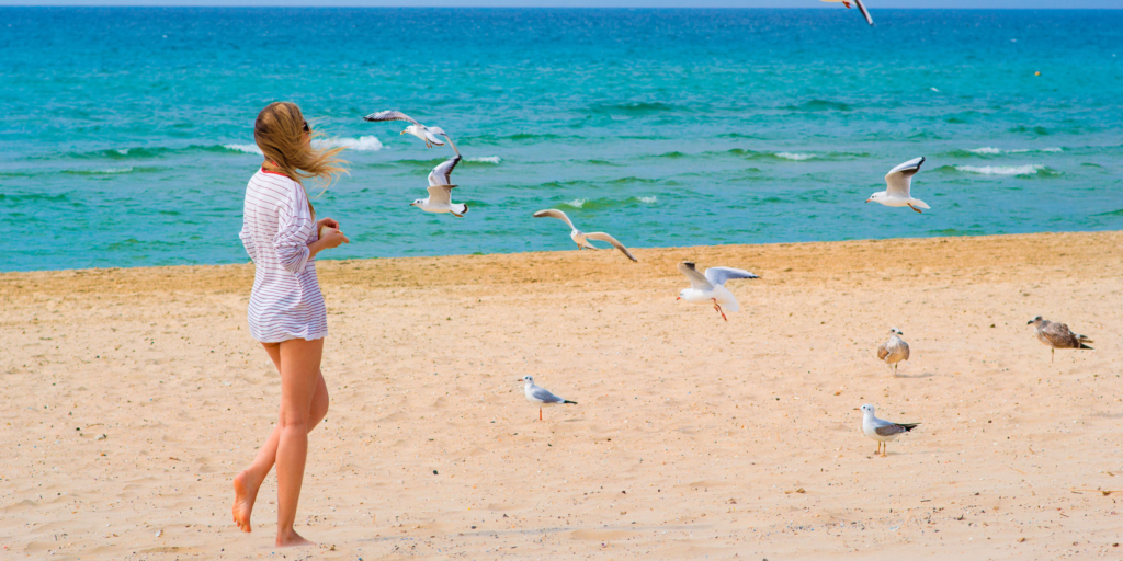 девушка на берегу моря с чайками